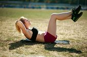 Young Woman Doing Press Fitness Exercise For Stomach Muscles On Grass Field