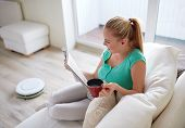 people, leisure, household and technology concept - happy woman reading magazine and drinking tea while robot vacuum cleaning floor at home