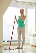 people, housework and housekeeping concept - happy woman with mop cleaning floor and calling on smartphone at home