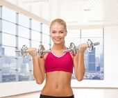 fitness, sport, fitness and people concept - smiling woman with dumbbells flexing biceps over gym or home background