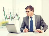 business, office and money concept - businessman in suit and black eyeglasses with laptop computer, papers, calculator and forex chart