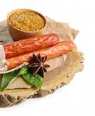 Smoked thin sausages, mustard in bowl and spices on wooden cutting board, isolated on white