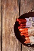 Assortment of thin sausages, and spices on plate, on wooden background