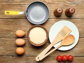 Food ingredients and kitchen utensils for cooking on wooden background