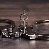 handcuffs and keys on brown wooden table background