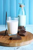 Glass and bottle of milk with chocolate chunks on cutting board and color wooden planks background
