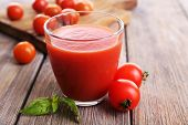 Tomato juice in glass with basil  and tomatoes cherry on wooden planks background