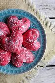 Cookies in form of heart in plate on color wooden table background