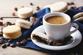 Gentle colorful macaroons and  coffee in mug on wooden table background
