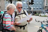 Vienna, Austria - July 12, 2014. Senior Couple With  Backpacks Looking  Map And City Guide .