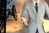 Businessman With Handshake To Cooperation and silhouette broadcasting satellite tower background