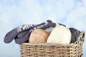 Knitting yarn and mittens in basket, on light background