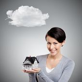 Young woman hands small toy house, isolated on grey background with cloud