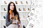 Woman keeps two stylish pumps in the shopping mall and can't choose the one for her. Big sales season