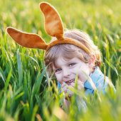 Adorable Little Boy With Easter Bunny Ears Playing In Green Grass