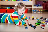 Funny Little Boy Playing With Lots Of Toy Cars Indoor