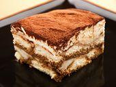 pic of unhealthy lifestyle  - Tiramisu cake in a black plate close up - JPG