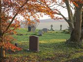 stock photo of graveyard  - The golden light of the setting sun shining upon a graveyard in England United Kingdom - JPG