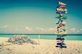 foto of wood pieces  - Funny directions signpost with distance to many different countries - JPG
