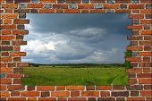 Broken Brick Wall And View To Field With Thunder