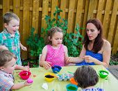 Children Painting Easter Eggs Outside With Mom