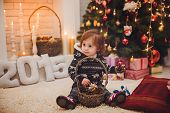 Beautiful mother with baby girl near a Christmas tree