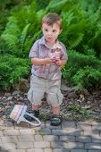 picture of easter basket eggs  - A happy boy with his Easter basket on the ground holds a purple Easter egg he finds during an Easter egg hunt activity in the spring season in a beautiful garden setting - JPG