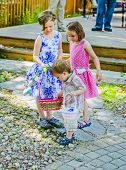 Little Boy Looking At A Little Girls Easter Eggs