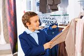 Cute smiling boy stands near clothes and choosing