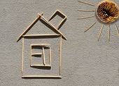 House and sun made of toothpicks on concrete