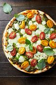 Cherry tomato and mozzarella pizza with basil pesto