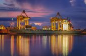 stock photo of export  - Container Cargo freight ship with working crane loading bridge in shipyard at dusk for Logistic Import Export background - JPG