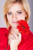 Close-up portrait of a woman with gerbera flower.