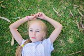 Caucasian little girl lay on grass
