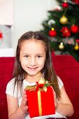 Little girl sitting on couch holding red box, gift, Christmas tree in the background