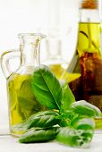 stock photo of flavor  - flavored olive oil WITH BASIL AND RED HOT PEPPER OVER WHITE - JPG