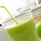 closeup of a glass with a fresh green smoothie for breakfast