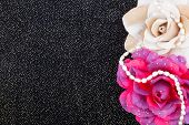 Black background with flowers and pearls