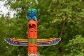 picture of totem pole  - Close up of Indian totem with forest in background  - JPG