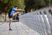 picture of stretch  - young athlete man stretching legs and warming up calf muscles before running workout leaning on bridge railing on city urban park working in summer morning training session - JPG