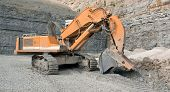stock photo of excavator  - a orange tracked excavator in a quarry - JPG