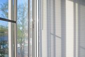 stock photo of louvers  - closed plastic blinds on the window with the reflection in the glass - JPG