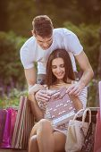 picture of sitting a bench  - A young girl sitting on a park bench enjoying the beautiful sunny day resting from shopping in addition to a bunch of shopping bags her boyfriend holding a gift bag and behind the bench leaning toward her face - JPG