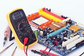 picture of  multimeter  - Digital multimeter and motherboard on a white background - JPG