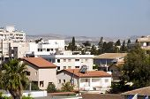 picture of larnaca  - rooftop cityscape view of Larnaca Cyprus hotels condos apartments offices Mediterranean sea and mountains in distance - JPG