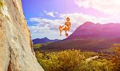foto of mountain-climber  - female rock climber hanging on a rope near the rocky wall on the mountain background - JPG