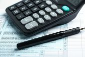 picture of income tax  - Individual income tax return form pen and calculator is on the desk - JPG