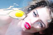 stock photo of human egg  - Adorable pretty cute girl with curly hair big beautiful eyes and bright pink lips looking through the flat glass surface with raw yellow yolk and white of an egg on blue background horizontal picture - JPG