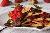 picture of crepes  - Crepes with fresh strawberries and chocolate topping macro on a plate - JPG