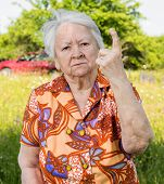 image of angry  - Old woman in angry gesture protecting her garden - JPG